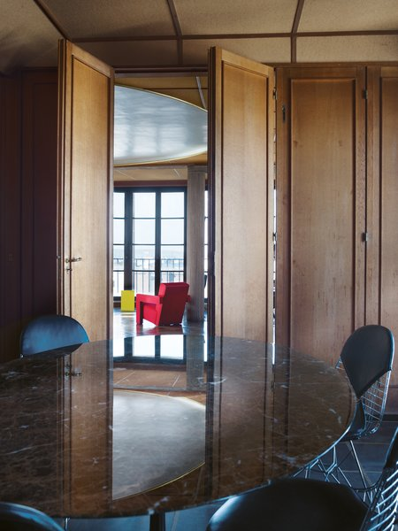 "In 2006, Claus—director of Claus en Kaan Architecten, one of the Netherlands' top architectural practices—finally got inside Perret's apartment. He was duly impressed. ""It's the sheer abundance with which limited materials are used here that first struck me,"" he says. ""The wall-to-wall French oak paneling, combined with materials that were ahead of their time—columns made not from marble but from stone-blasted concrete, the extraordinary round plaster ceiling inset, and the fiber-wood paneling—and his attention to the tiniest of details.""  He tracked down the organization that owns the apartment, the Association Auguste Perret, to see if he and his wife could rent the unit as a pied-à-terre. To his surprise, they said yes.   In the dining room, a marble-topped table by Eero Saarinen is ringed with Eames wire chairs. Through oak accordion doors, the atrium beckons with red Utrecht armchairs by Gerrit Rietveld and a yellow Diana table by Konstantin Grcic."