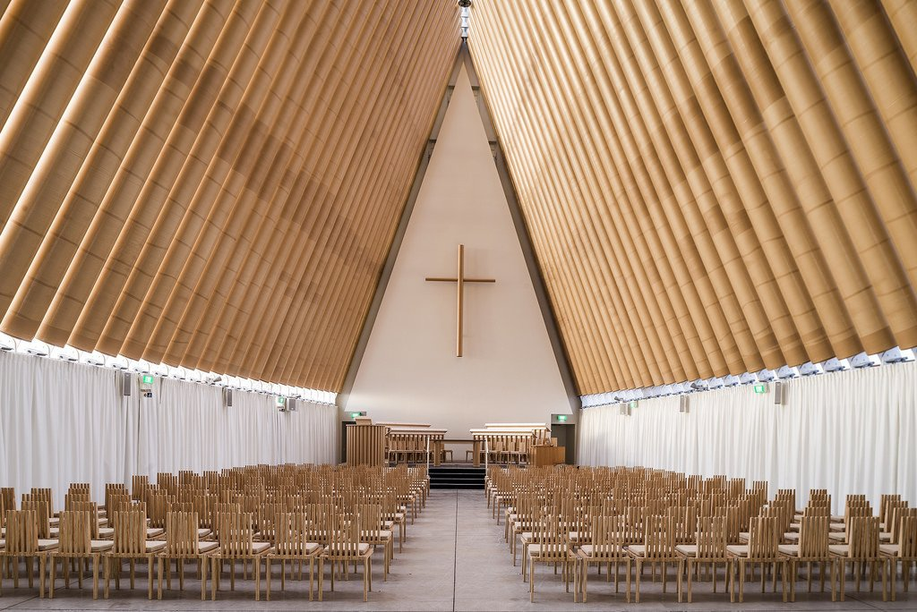 "Cardboard Cathedral (Christchurch, New Zealand: 2013)  After a massive earthquake destroyed this New Zealand town's landmark 19th-century cathedral in 2011, Ban crafted an A-frame out of cardboard tubing and shipping containers, a landmark example of his ""emergency architecture."" In another nod to resiliency and symbolic rebirth, the stained glass triangle at the front of the church incorporates imagery from the former cathedral's famous rose window. 11 Buildings by Shigeru Ban - Photo 1 of 11"