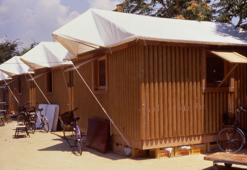 Paper Log House (Kobe, Japan: 1995)  These 16-square-meter structures elegantly proved Ban's cardboard concept; tubing could be used as load-bearing structures, and could be made both waterproof and flame-resistant. Beer crates were used for support. Ban supposedly picked Kirin because the label colors were a better match. This design has since been used for disaster relief in India and Turkey.  Credit: Forgemind Archimedia, Creative Commons
