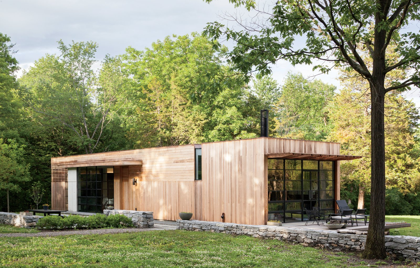In realizing their dream to build a country retreat in upstate New York, Sandy Chilewich and Joe Sultan—proprietors of the textiles firm Chilewich|Sultan—eschewed a mountainous view for an understated wooded plot. At 800 square feet, the flat-roofed home is a modest structure for the expansive 10-acre property. Tagged: Exterior, House, Flat RoofLine, and Wood Siding Material.  Superb Single-Story Homes by Luke Hopping from An Architect's Tips for Keeping Your Electric Bills Down