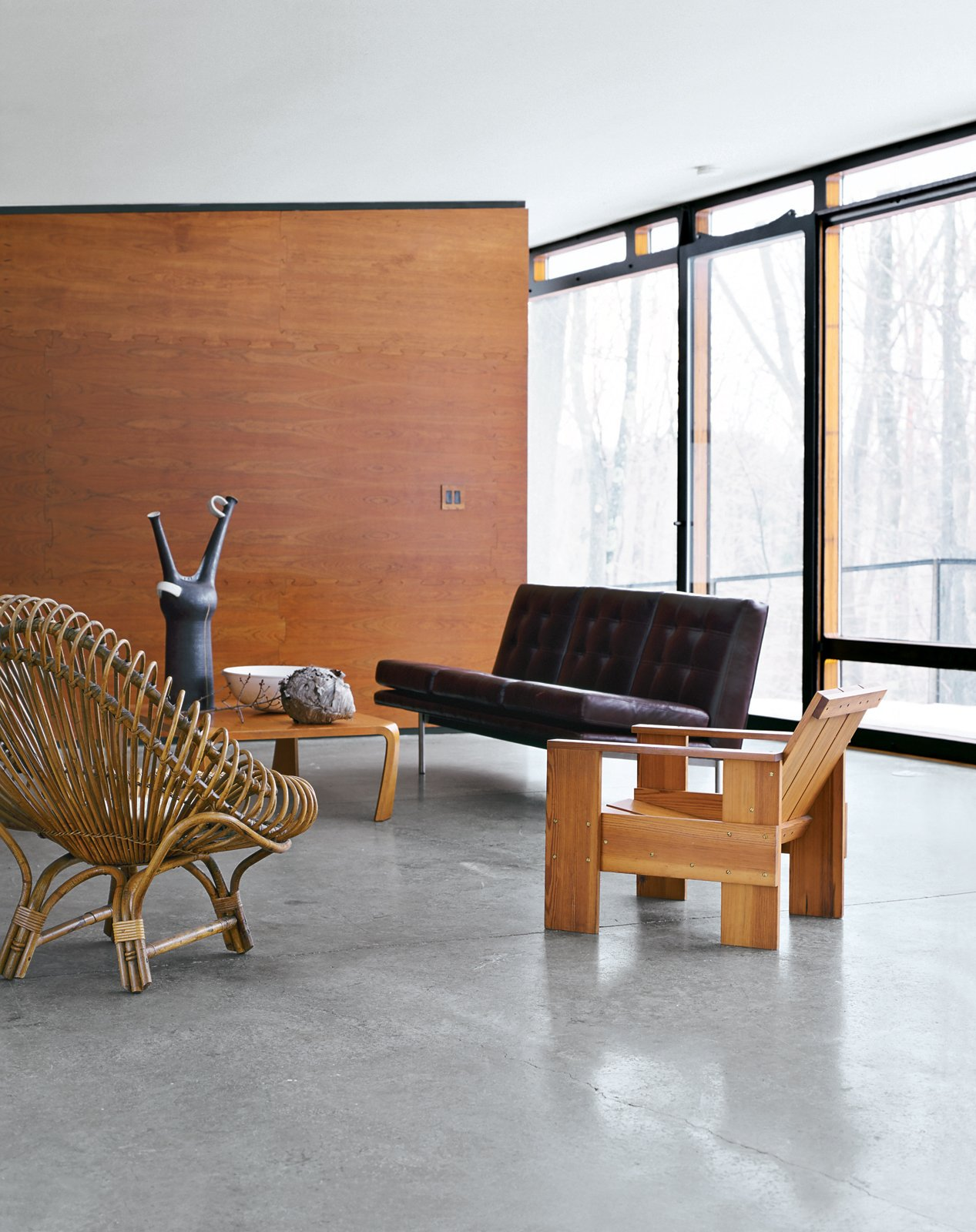Architect William Massie built a hybrid prefab home for vintage retailer Greg Wooten, who handled the interiors. In the living room is a 1950s Franco Albini rattan chair, a Crate chair designed by Gerrit Rietveld in 1934, and a 1970s sofa by Edward Axel Roffman. The tall ceramic piece is by Bruno Gambone. Tagged: Living Room, Sofa, Chair, and Concrete Floor.  Photo 3 of 12 in A Hybrid Prefab Home in Upstate New York