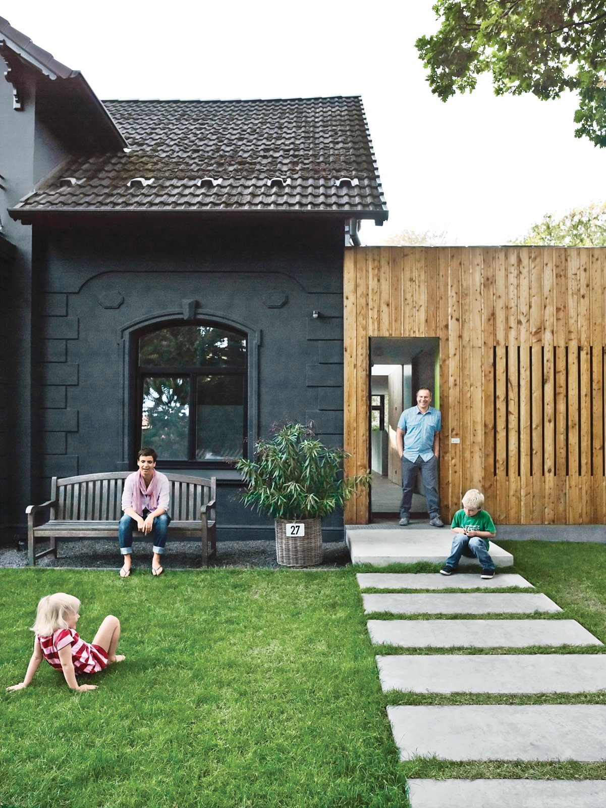 A family of cost-conscious Hamburgers converted a kitschy turn-of-the-century villa into a high-design home with a strict budget in place. To unite the quaint masonry of the original villa with the squat, ugly add-on built flush against it, the architects decided to paint the old-fashioned facade graphite gray and then covered the box next door in plain, light-colored larch. Photo by Mark Seelen.  All-Clad: 7 Innovative Exteriors by Kelsey Keith from Paint it Black