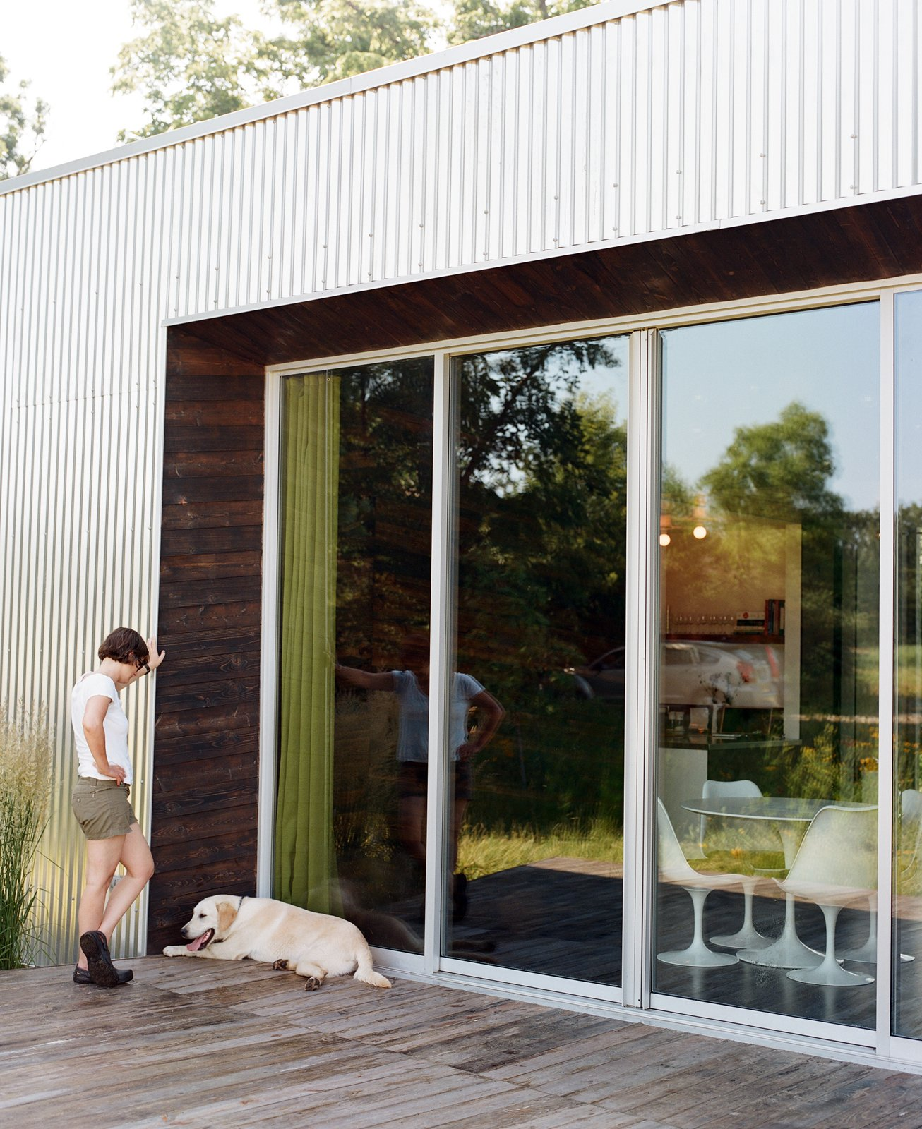 Out on the deck, Pascal enjoys some relaxed time with their dog, taking a breather in a bit of shade while sun streams across the meadow.  Photo 11 of 25 in 25 Dogs Living in the Modern World from How To: Inviting Front Doors for Modern Homes