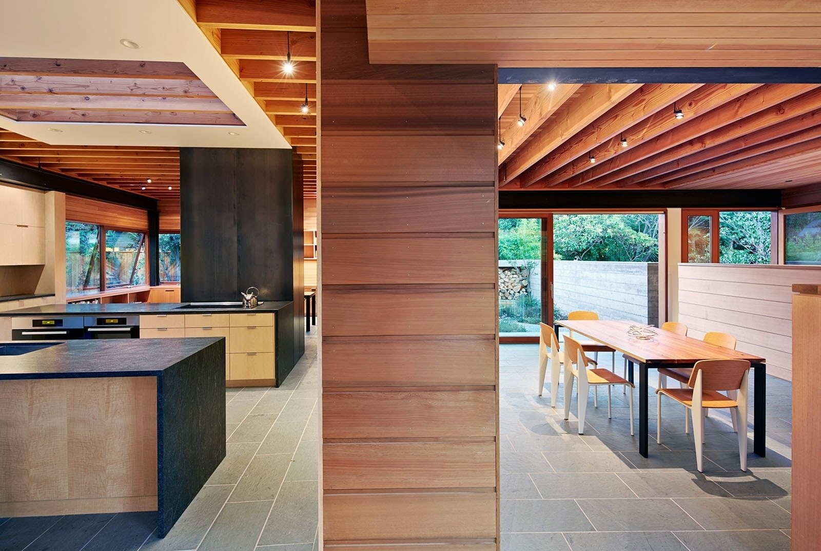 The first floor consists of two long and narrow structures that intersect in an open kitchen, providing distinct programmatic areas and settling into the tree-lined landscape, allowing yards to surround and permeate each room. Tagged: Kitchen, Wood Cabinet, and Slate Floor.  Photo 2 of 8 in A Sustainable Home in Silicon Valley