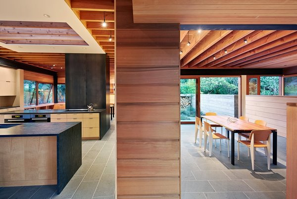 The first floor consists of two long and narrow structures that intersect in an open kitchen, providing distinct programmatic areas and settling into the tree-lined landscape, allowing yards to surround and permeate each room.