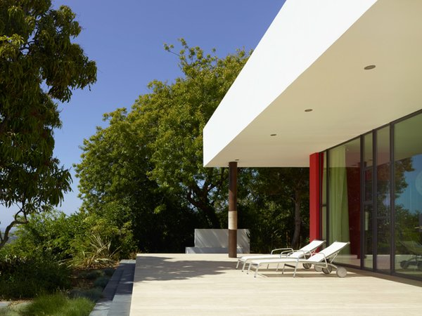 On the sunset side of the Sunrise house, the home's west terrace is shaded by mango trees.