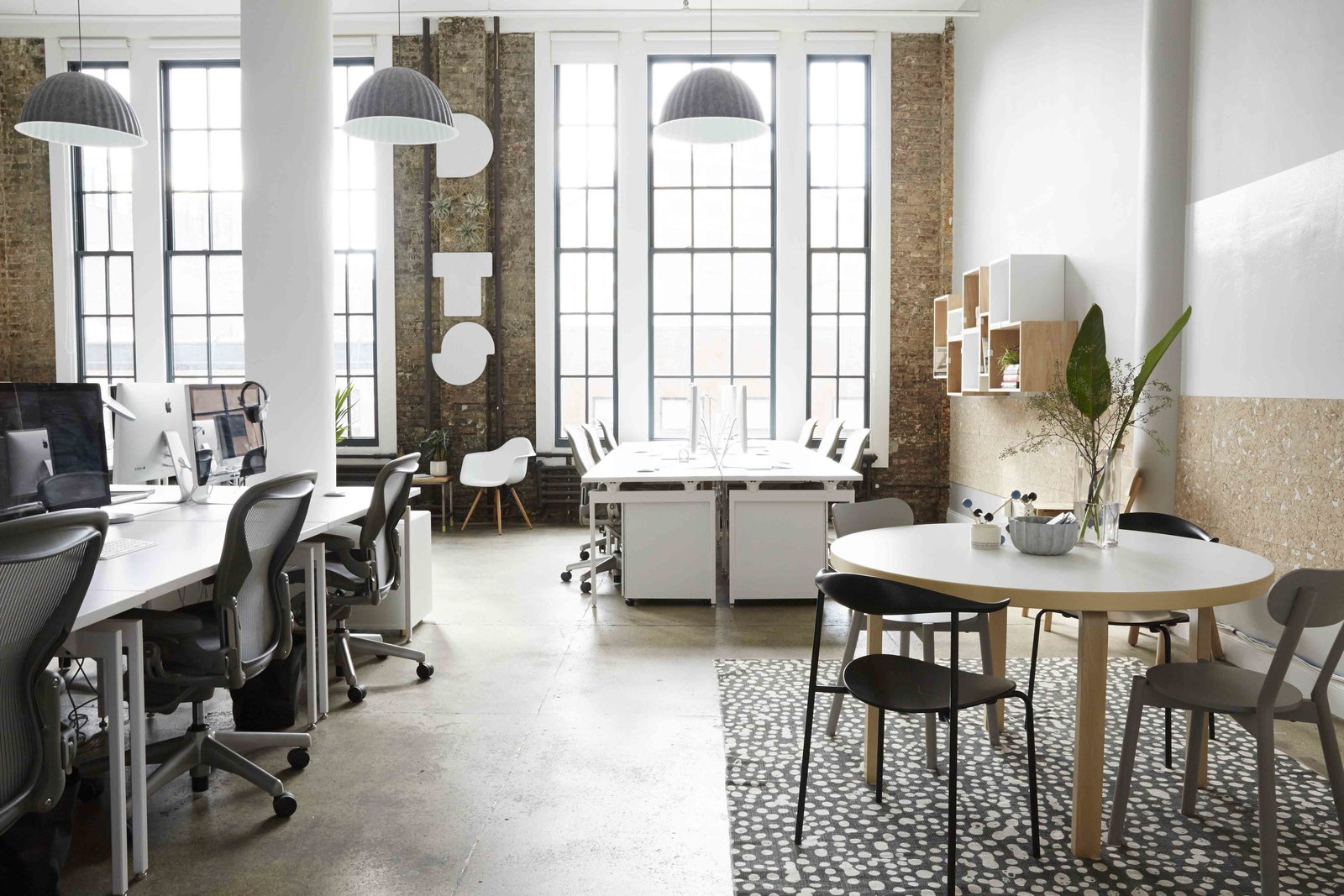 """The new office makes the most of the exposed brick, tall ceilings, and large southfacing windows. """"Because we are based in New York, we don't have a ton of space,"""" says Dots co-founder Patrick Moberg. """"We wanted a clean, thoughtfully designed place to build and play games."""" Murphy interpreted these wishes into an aesthetic she describes as """"traditional American office meets Scandinavian home.""""  Office by Mark Lincoln from Scandinavian-Inspired Office Design in NYC"""