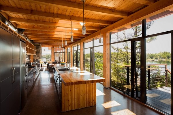 The home maintains remarkable material consistency, with Douglas fir cladding the beams, kitchen countertop, and interior walls. The open-plan kitchen absorbs views of the lake through an expansive glass wall. Photo 2 of Monument Channel Cottage modern home