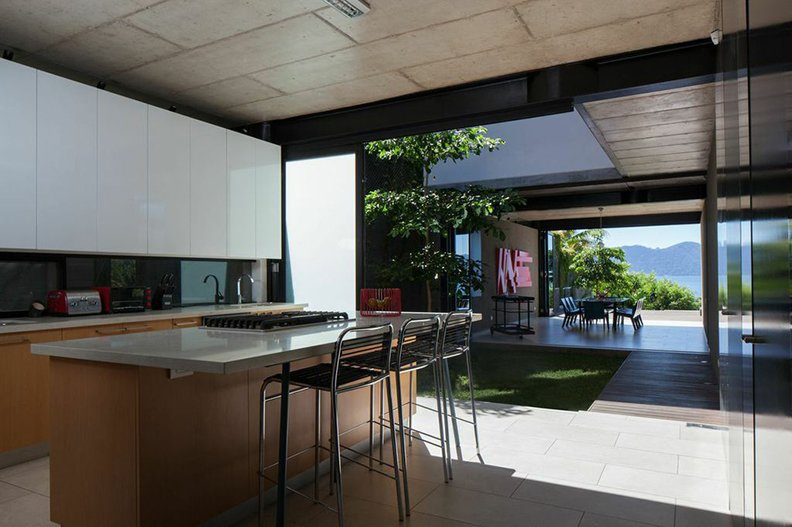 The kitchen, the heart of the house, has a direct view of the adjacent lake. Quartz countertops are paired with lacquered MDF cabinets.  Kitchens with Killer Views by Andrea Smith