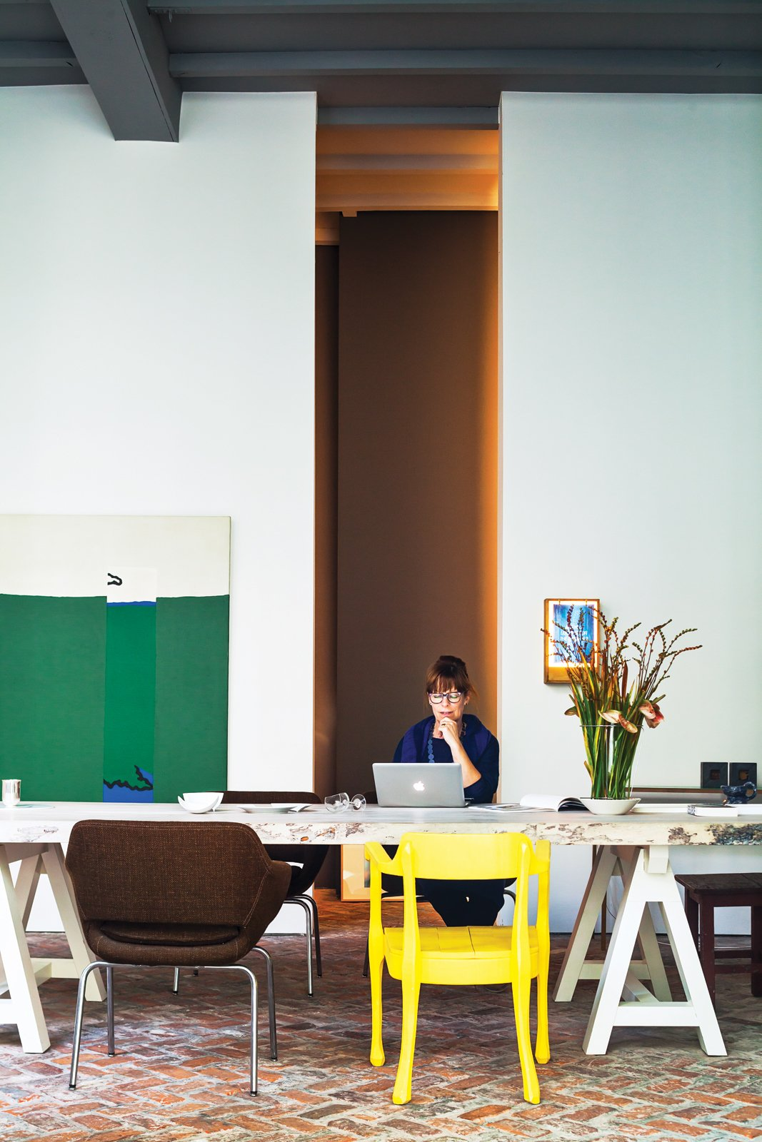 With the help of architect Bart Lens, Veerle Wenes and Bob Christiaens merged a 19th-century building with a 1970s one to create a combined home and art gallery in Antwerp. In the dining room downstairs, Wenes entertains family, friends, and gallery visitors. The yellow chair is by Jens Fager. Tagged: Office, Desk, and Chair.  Photo 3 of 19 in This House Proves Art Galleries Can Be Super-Friendly