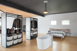In the bedroom, an improbably placed tub is situated in front of two closets that can easily be maneuvered thanks to skateboard wheels affixed to the underside.