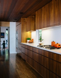 In the kitchen, interior designer Emily Knudsen Leland replaced purple laminate cabinets with flat-sawn eastern walnut, and added PentalQuartz countertops in polished Super White for contrast. The cooktop and oven are from Miele.