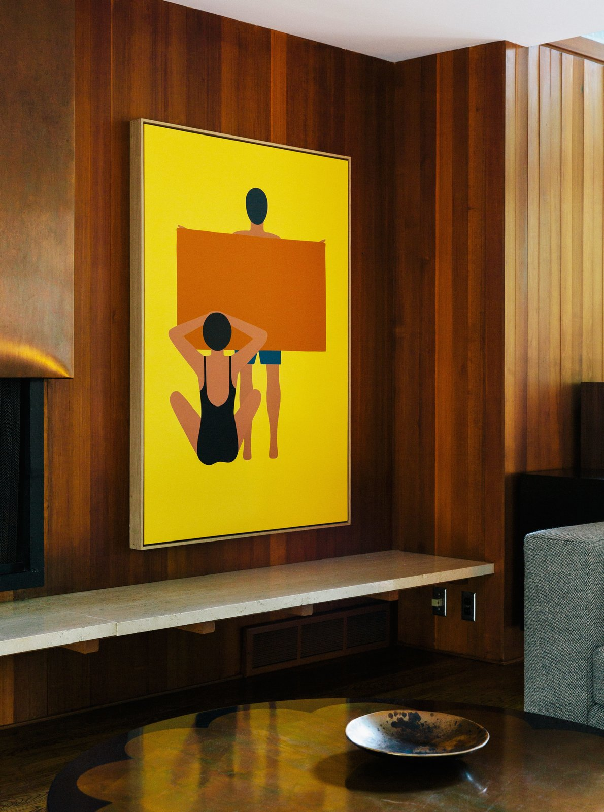 "In the living room, the painting is by Geoff McFetridge and the wood paneling is original to the house. ""Jewel-y color and simple shapes—they feel right in this house,"" says interior designer Jessica Helgerson. Wood Paneling Loses its Dated Reputation with This Renovation of a 1959 Portland Gem - Photo 4 of 11"
