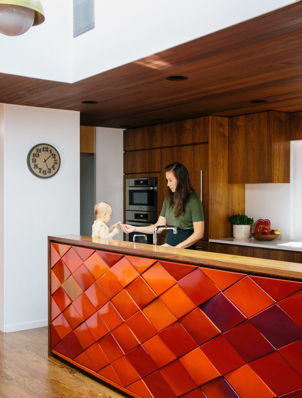 In the kitchen, Yuka makes baby Maude a snack at an island with original red tiles. Hanging cabinets were removed to maximize light and family-room views. Tagged: Kitchen, Wood Cabinet, Medium Hardwood Floor, Wall Oven, Ceiling Lighting, Recessed Lighting, and Pendant Lighting.  Photo 8 of 11 in Wood Paneling Loses its Dated Reputation with This Renovation of a 1959 Portland Gem
