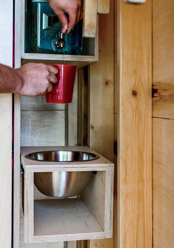 One corner holds a refillable water jug and a stainless-steel washbasin. Camping with Dad Just Got Cooler - Photo 6 of 10