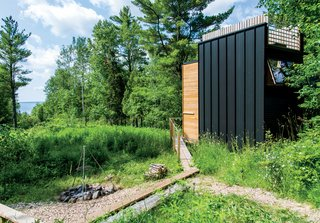 101 Best Modern Cabins - Photo 60 of 101 - A standing-seam steel roofing panel clads a portion of the exterior, while the aluminum pipes also serve as the railing for the roof deck. The family cooks all their meals at the fire pit outside.