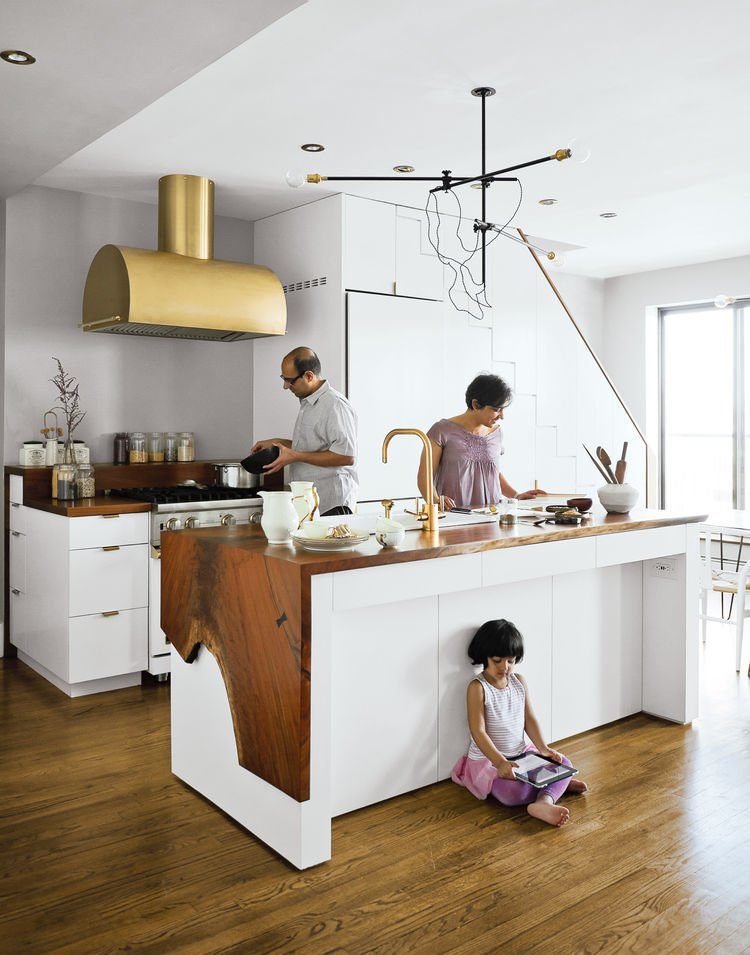 The Mandayam–Vohra family's Brooklyn kitchen is highlighted by a gold hood that complements Workstead's signature three-arm chandelier, shown here in its horizontal configuration. Tagged: Kitchen, Wood Counter, Medium Hardwood Floor, White Cabinet, Range Hood, Range, Vessel Sink, Pendant Lighting, and Recessed Lighting.  Photo 19 of 21 in 20 Dream Kitchens from Ways to Use Gold Accents in the Kitchen