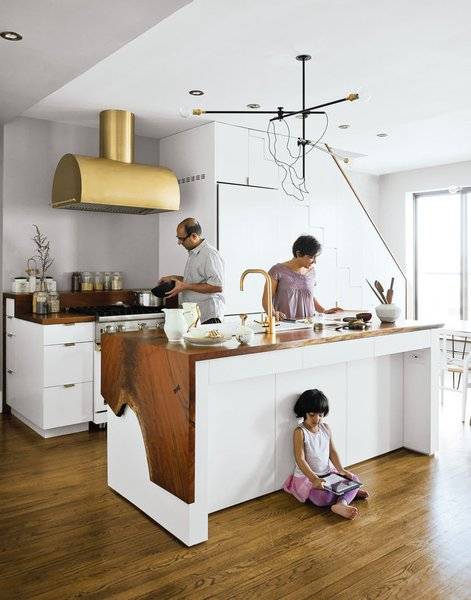 The Mandayam–Vohra family's Brooklyn kitchen is highlighted by a gold hood that complements Workstead's signature three-arm chandelier, shown here in its horizontal configuration.