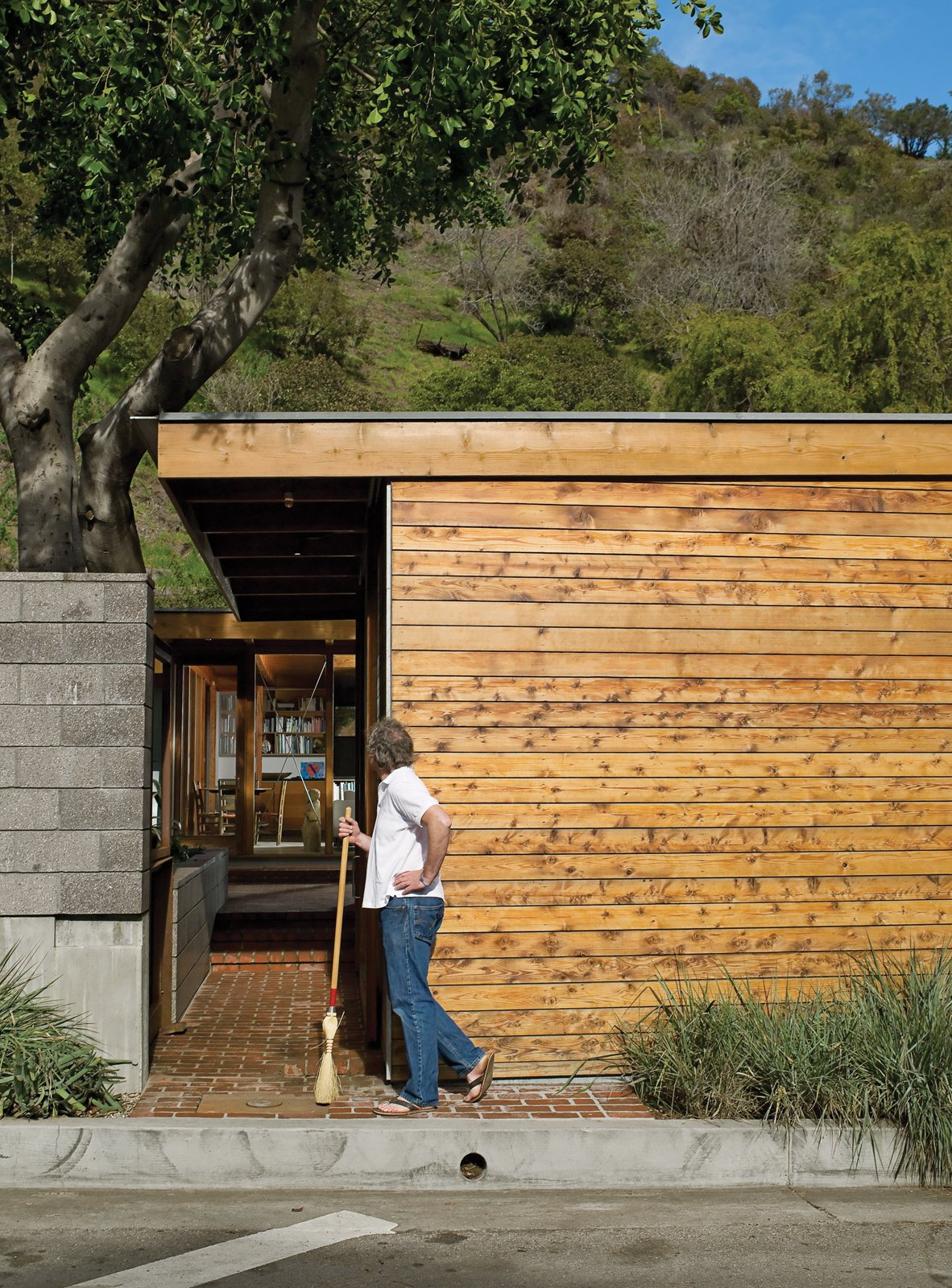 Flanking the concrete wall is a carport and an entrance leading past a small, cedar-clad ancillary building for art projects and laundry.