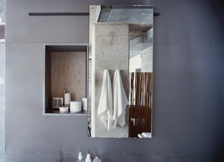 The Hill Bathroom - Photo 6 of 12 - The door to Hill's medicine cabinet, made by George Sacaris, slides open to reveal a concrete wall.