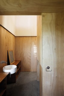 Minimalist doesn't have to mean monochromatic or marble. The Gaboon-plywood walls of the McKenzie residence in New Zealand flow through into the bathroom without a door to get in the way.