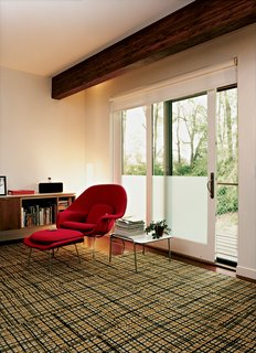 An Eero Saarinen Womb chair sits in the master bedroom, which also has a small office space.
