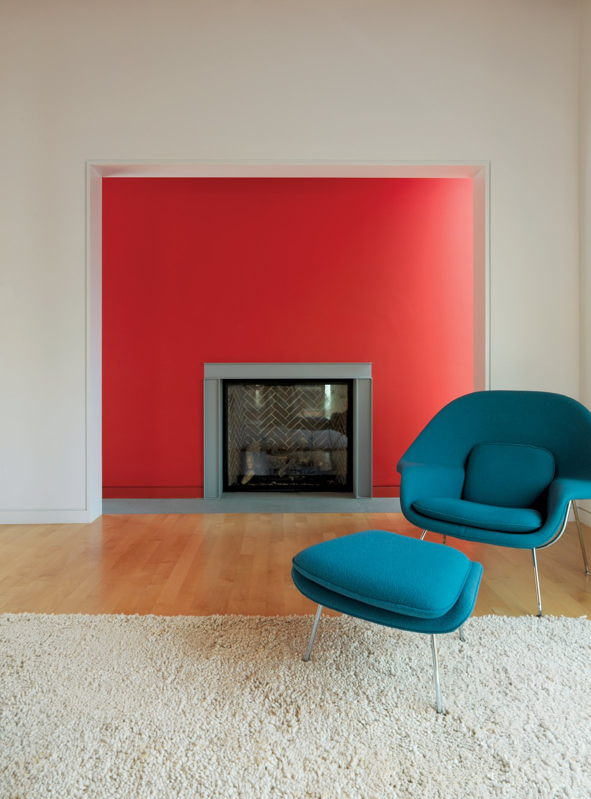 In the living room, Fashandi enjoys lounging in the Saarinen Womb chair by Knoll near the fireplace. The red wall is flanked by thin windows, causing it to glow in the sunlight. Tagged: Living Room, Standard Layout Fireplace, Light Hardwood Floor, Rug Floor, and Chair.  Photo 14 of 16 in Family Matters