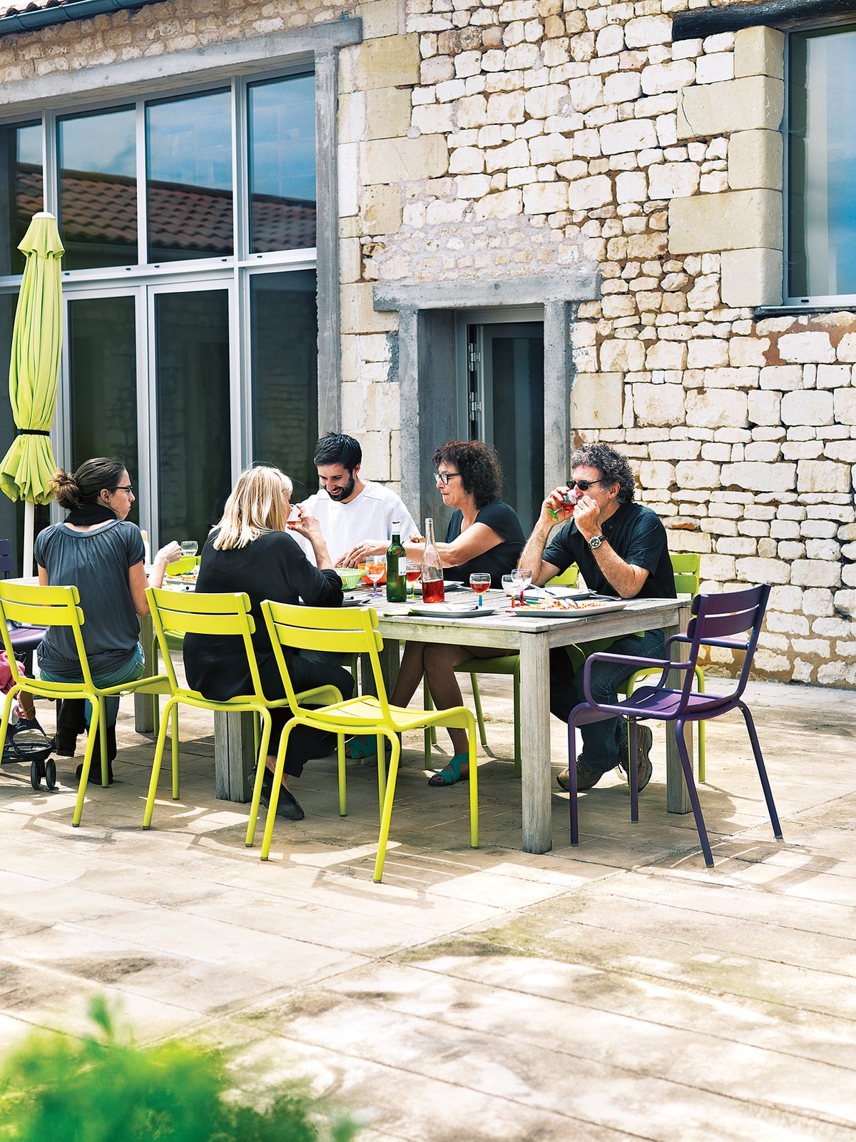 Monory's friends, the Leclercs, join her for an alfresco meal on the patio. They're seated at a custom-made table on Fermob's Luxembourg chairs.  Photo 7 of 12 in Matali Crasset Renovates Monory Farmhouse