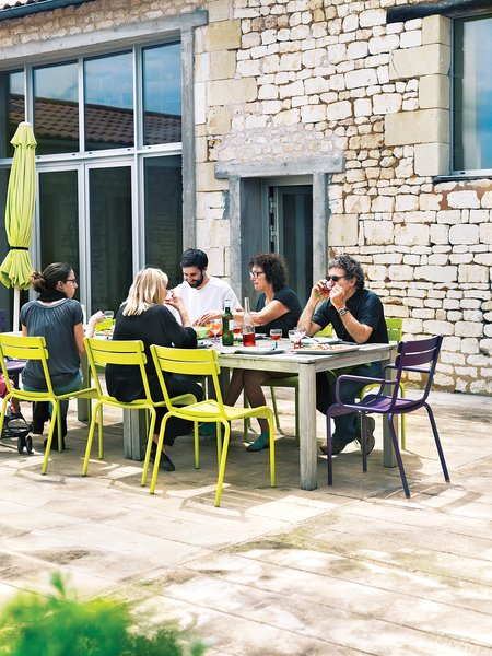 Monory's friends, the Leclercs, join her for an alfresco meal on the patio. They're seated at a custom-made table on Fermob's Luxembourg chairs.