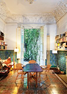 In the dining room, which opens to the backyard terrace, original tilework on the floors and walls complement decidedly modern counterparts—an original 1938 Butterfly chair <br><br>by Antonio Bonet, Juan Kurchan, and Jorge Ferrari Hardoy, and a 1983 TMC floor lamp by Spanish designer Miguel Milá.