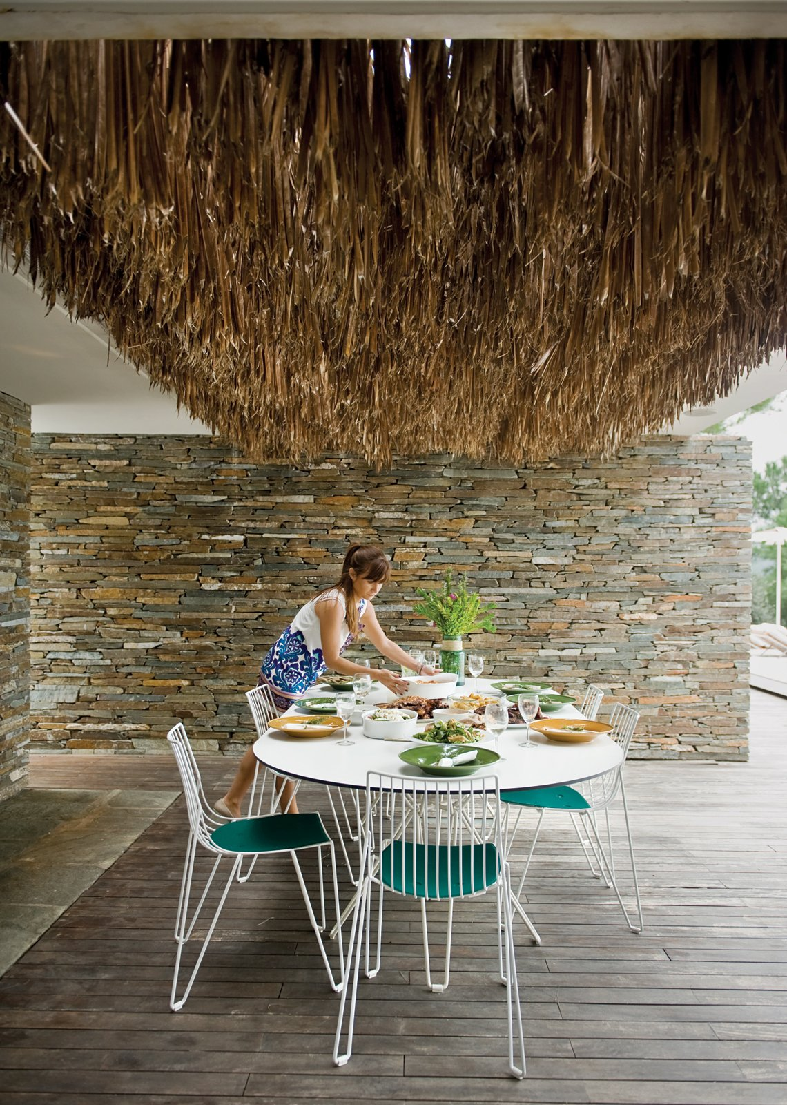 The Mourtzouchoses entertain constantly, which means that food is rarely far from anyone's mind. Alexia sets a Tio table (with matching chairs) by Massproductions, over which hangs a thatch of dried palm fronds.  Photo 7 of 13 in An Idyllic Vacation Home in Greece