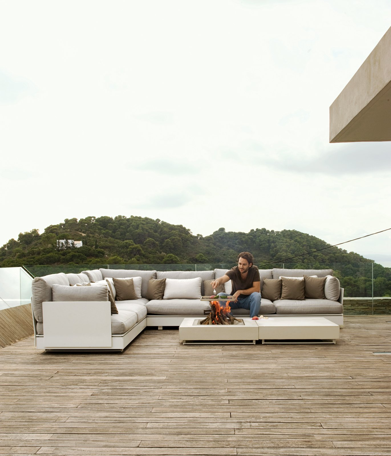 Life at the Plane House is all about relaxing and hanging out with friends for co-owner and Athenian Achilleas Mourtzouchos. Here he does a bit of lounge-side grilling on a modular Pure seating system by Viteo. Even the fire table and grill are part of the Austrian outdoor furniture company's line.  Photo 3 of 13 in An Idyllic Vacation Home in Greece