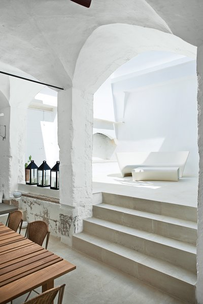 Modern Meets Ancient in a Renovated Italian Vacation Home - Photo 4 of 8 - The indoor-outdoor Grand Plié sofa and Piaffé table, which the couple designed for Driade, perfectly suit the whitewashed courtyard, with curving silhouettes that echo the surrounding stonework. Serafini and Palomba purchased the metal lanterns at a local market.