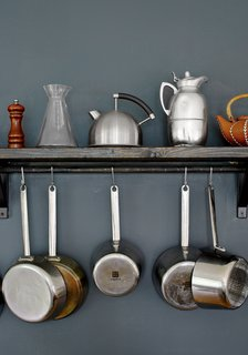 Modern Meets Traditional in a Swedish Summer House - Photo 9 of 11 - Small kettles and metal pots rest and hang on a wooden shelf in the kitchen.