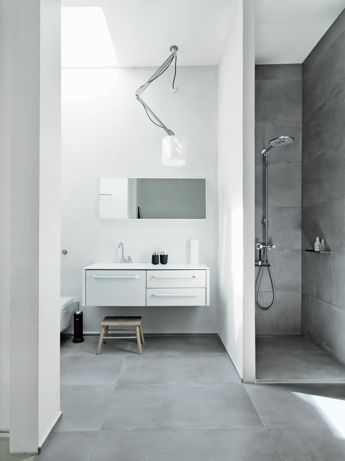 The family shares one main bathroom, which is outfitted with Vipp's new line of products: 982 bath furniture, a 906 faucet, and a 992 mirror. The shower sports a Raindance Connect showerhead by Hansgrohe, and there is a wall-mounted toilet by Villeroy & Boch. The Nomad light fixture is from Modular Lighting Instruments, and the floors are topped with ceramic tiles by LaFaenza.  Storage by Dwell from Converted Loft Fit for a Modern Family in Copenhagen