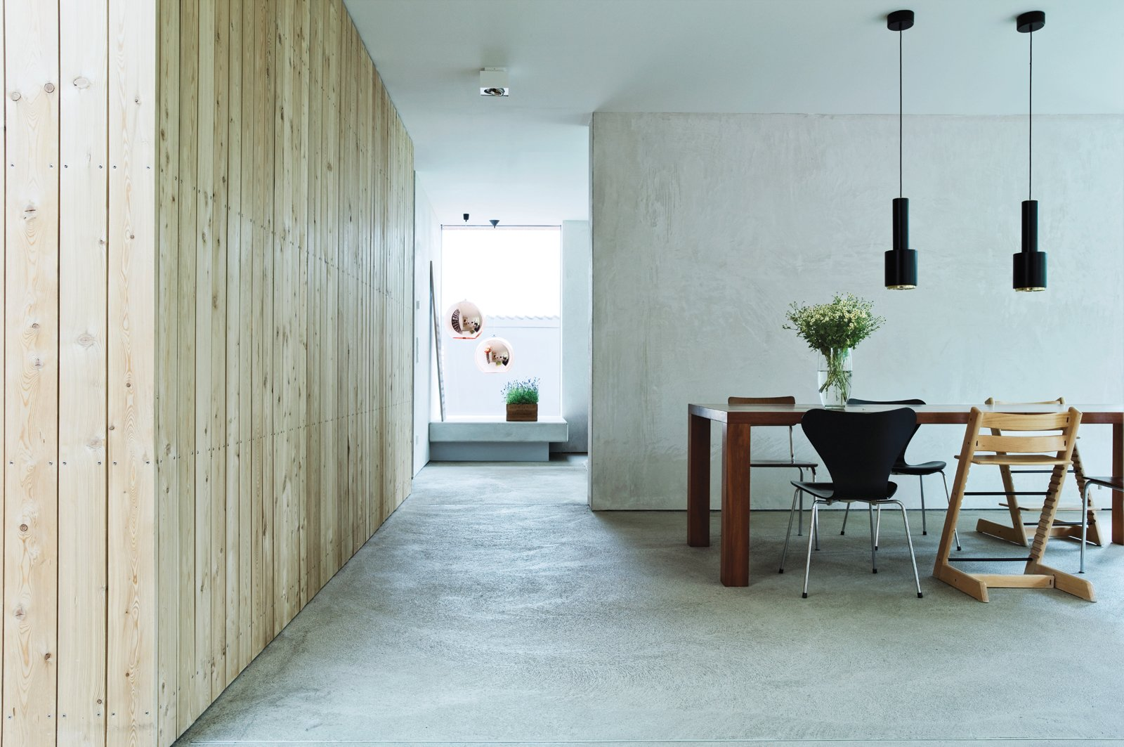 """Idée Concrète  To get a concrete look for the floors throughout the house, the team first considered Pandomo flooring, a slick treat-ment that would be even more expensive than a standard finish. Instead, says Winterhalder, they experimented with raw materials. """"I'd call the suppliers and say, 'Do you have something grayer?' They thought I was crazy."""" In the end, instead of a concrete look, the couple went with actual concrete—at a fifth of the price.   pandomo.de Paint it Black - Photo 5 of 10"""