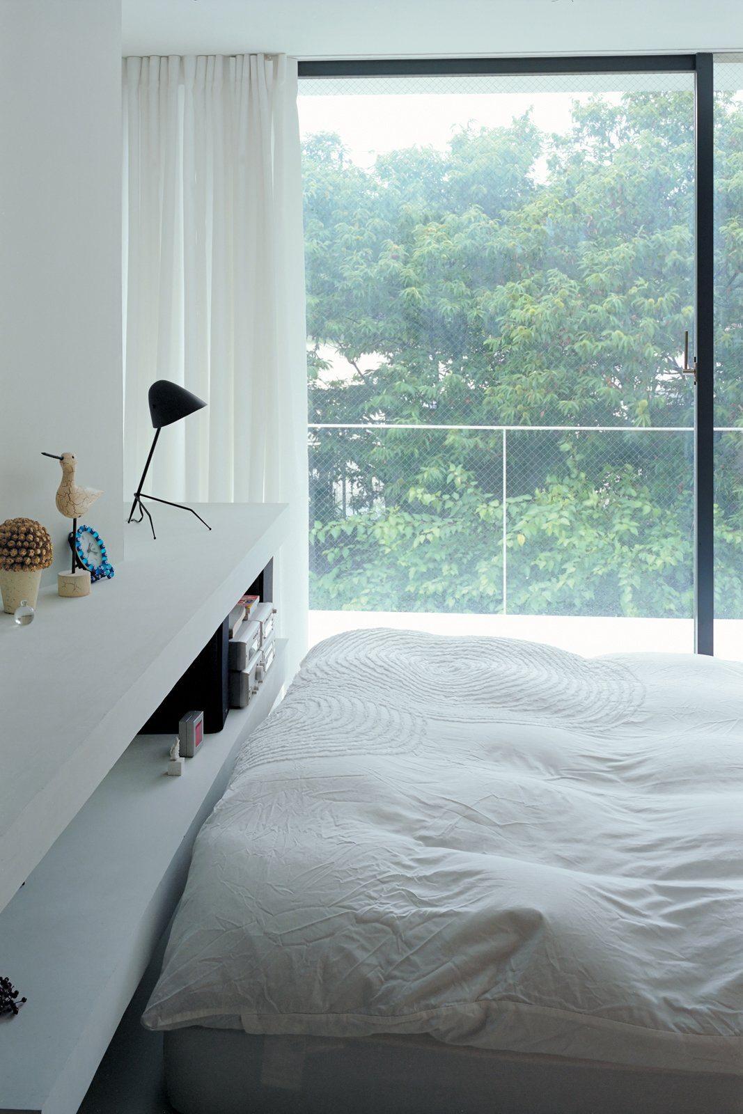The bedroom has a view of the cherry trees.  Photo 9 of 11 in Small Space Live/Work Box Home in Japan