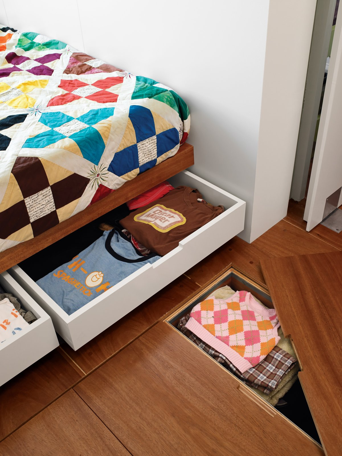 Storage under the bed and floor hides clutter in the master bedroom.  Photo 2 of 11 in 10 Ways to Solve Storage Problems in Small Spaces