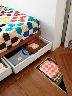 Storage under the bed and floor hides clutter in the master bedroom.