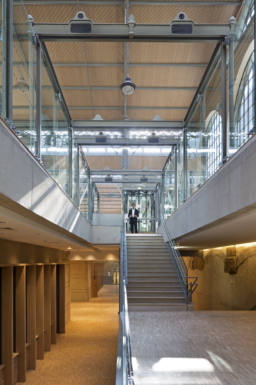 Carreau du Temple's Main Level and Basement  With the addition of a bi-level basement containing all the working elements of the structure, the ground-level mezzanine remains unencumbered and adaptable.  Photo Credit: Fernando Javier Urquijo/studioMilou architecture.