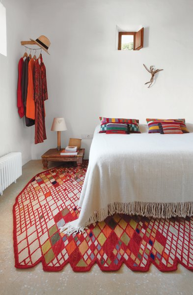 A Losanges rug by Ronan and Erwan Bouroullec, part of Nani Marquina's 2001 collection, anchors the master bedroom. The Basica Minima bedside lamp is from Santa & Cole, and the kilim pillows are by Philippe Xerri.