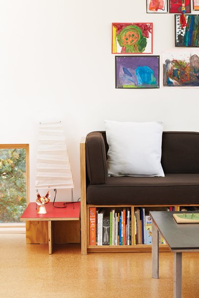 In the living room, an Akari lamp by Isamu Noguchi sits atop a coffee table Hale made and next to a collage of Maisie and Pippa's paintings. Like most of the furniture in the house, the couch, coffee table, and side table were made by Hale or his close colleagues, often in his favorite material: plywood.