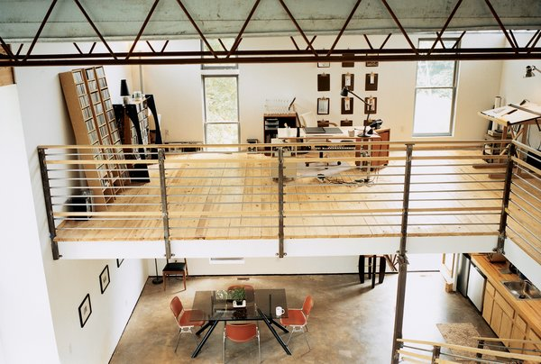The bedroom overlooks an office, which floats above the kitchen and dining room. The railing and banister were fabricated by a local metal worker a few miles away.