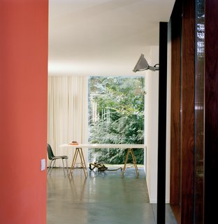Van Everbroeck's home office occupies the end of one arm of the building. An industrial outdoor light fixture is mounted on a black-painted steel post. The orange of the back wall was chosen to work with the glowing rays of the sunset and the silhouetted, dancing shadows of leaves.