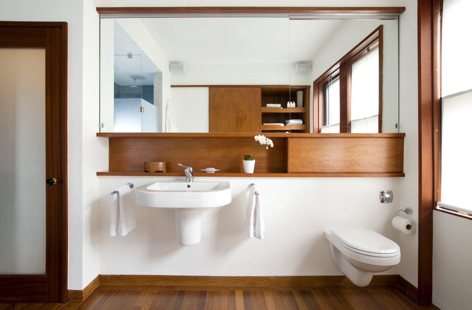 """Whenever you're making a minimal bathroom, you always have issues with storage,"" Klug says. The wall-hung Duravitsink leaves no place ""to put all your junk,"" so Klug and Butz added small shelf above. The space to the right, which appears as an extension of the shelf is actually a panel that hides access to the water tank of the wall-hung toilet, also by Duravit.Photo by   Eric Roth  Photo 3 of 4 in Loo & Improved"