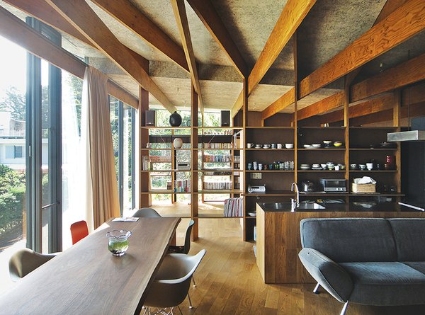 In the open living and dining room of a hillside family home in Japan, Eames shell chairs surround a custom walnut table by Kagura.
