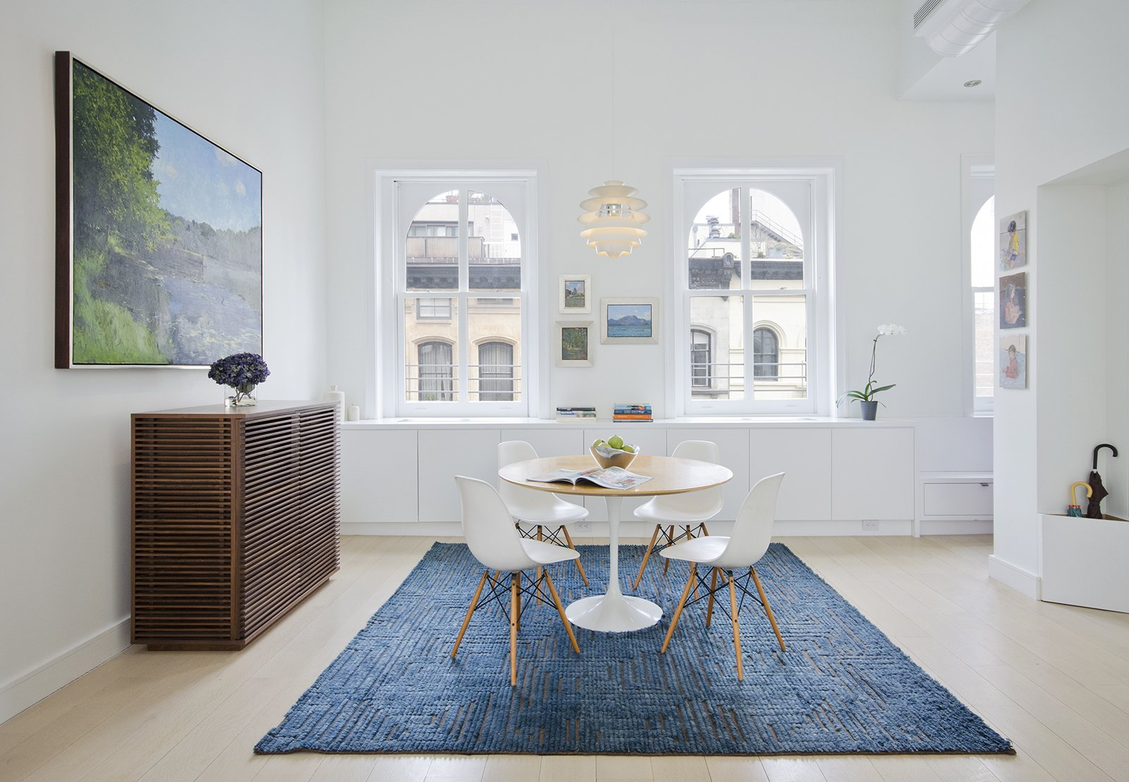 In a renovated Tribeca loft, Eames shell chairs surround a Saarinen Tulip table from Knoll. The Line console is from Design Within Reach and the pendant light is Louis Poulsen's Snowball. While architect Matthew Miller of New York firm StudioLAB gutted the space, some of the original details—like the windows—remain. The rug is from ABC Home. Tagged: Dining Room, Chair, Pendant Lighting, Table, and Light Hardwood Floor.  Photo 3 of 9 in The Complete Dwell Guide to Eames Shellspotting