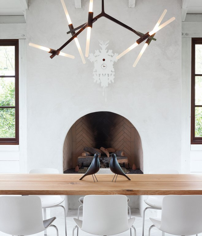 The home's informal dining space has a slightly rustic feel, sporting bronze and wood in the form of a Lindsey Adams Adelman chandelier for Roll & Hill and a table by Terry Dwan, mixed with folk-art touches like the Eames House Birds and a cuckoo clock from Diamantini & Domeniconi. Photo by Gregory Miller
