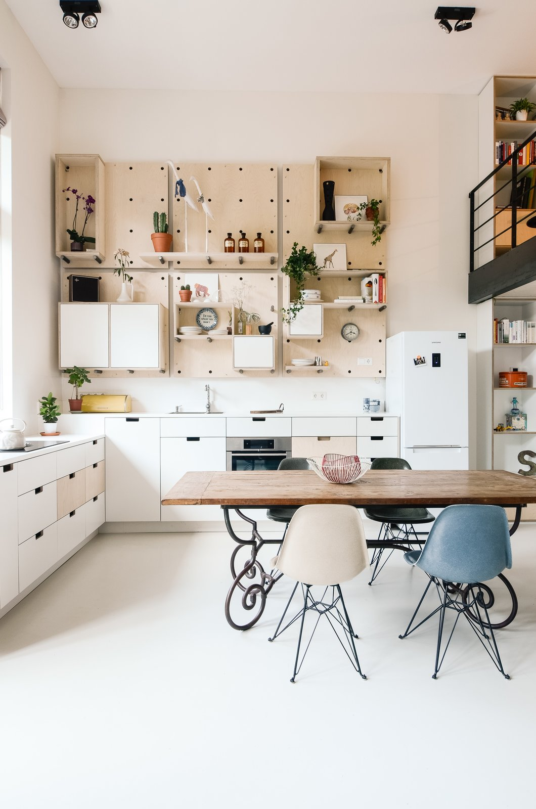 The kitchen is completely open to the main living area and features a custom birch pegboard wall. Eames dining chairs accent the space. Tagged: Kitchen, Refrigerator, White Cabinet, Open Cabinet, and Ceiling Lighting.  Photo 4 of 21 in 20 Dream Kitchens from Schoolhouses Turned into Modern Homes