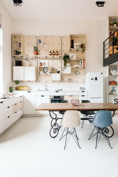 The kitchen is completely open to the main living area and features a custom birch pegboard wall. Eames dining chairs accent the space.